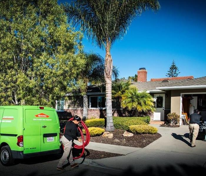 SERVPRO van parked in front of a home while technicians unload equipment
