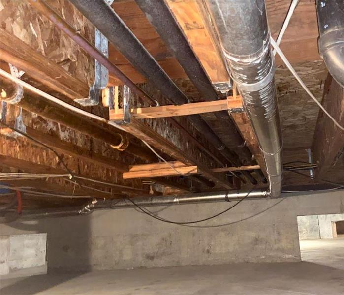 picture of a crawl space with water damaged joists